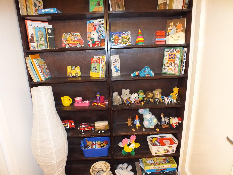 Játékpolc telis tele sok játékkal és mesekönyvvel.